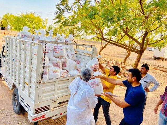 Contadini indiani della famiglia Manda caricano sacchi di cibo su un camion per aiutare i bisognosi durante il lockdown. (Per gentile concessione di Ramnivas Manda)
